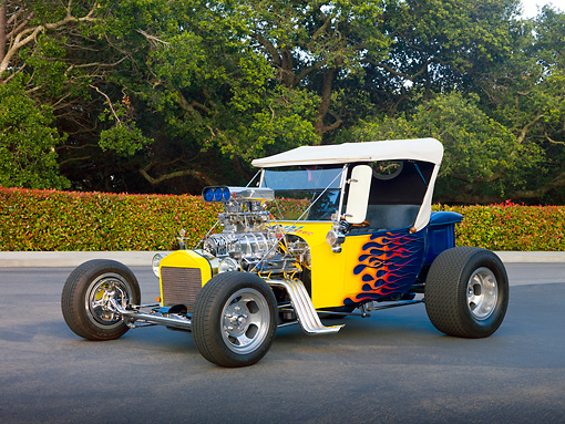 AUT 26 RK3040 01 © Kimball Stock 1923 Ford T-Bucket Hot Rod Blue With Yellow Flames 3/4 Front View On Pavement By Trees