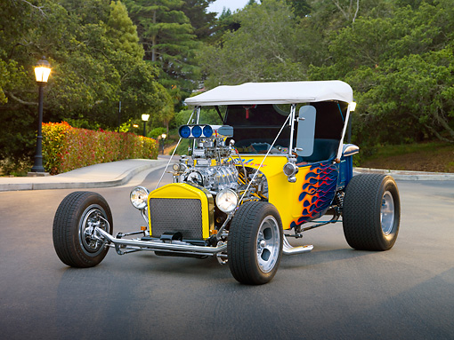 AUT 26 RK3041 01 © Kimball Stock 1923 Ford T-Bucket Hot Rod Blue With Yellow Flames 3/4 Front View On Pavement By Trees And Street Lamps