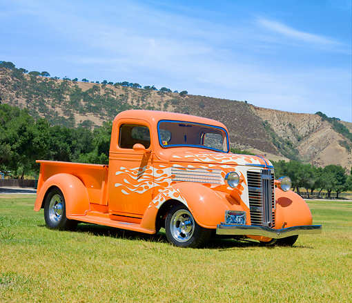 AUT 26 RK3045 01 © Kimball Stock 1937 GMC Pickup Truck Orange With White Flames 3/4 Front View On Grass By Hills