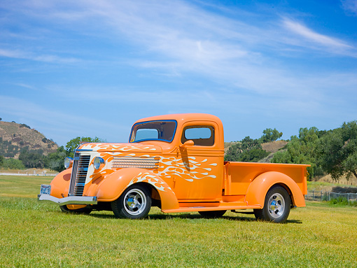 AUT 26 RK3046 01 © Kimball Stock 1937 GMC Pickup Truck Orange With White Flames 3/4 Side View On Grass By Hills