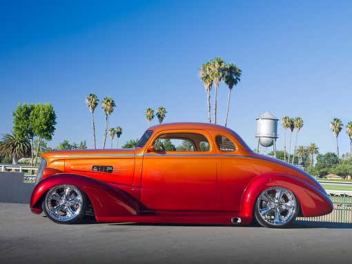 AUT 26 RK3064 01 © Kimball Stock 1937 Chevrolet Coupe Candy Red And Tangerine Profile View On Pavement By Palm Trees And Water Tower