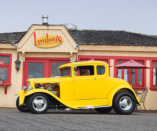 AUT 26 RK3105 01 © Kimball Stock 1930 Ford Model A 5 Window Coupe Yellow Profile View On Pavement By Restaurant