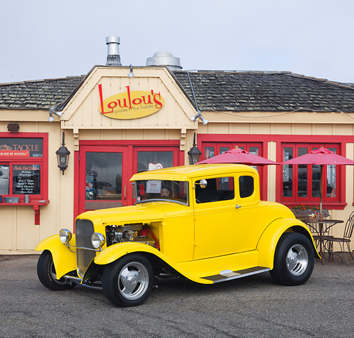 AUT 26 RK3106 01 © Kimball Stock 1930 Ford Model A 5 Window Coupe Yellow 3/4 Front View On Pavement By Restaurant