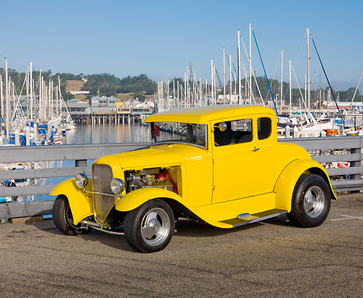 AUT 26 RK3107 01 © Kimball Stock 1930 Ford Model A 5 Window Coupe Yellow 3/4 Front View On Pavement By Harbor