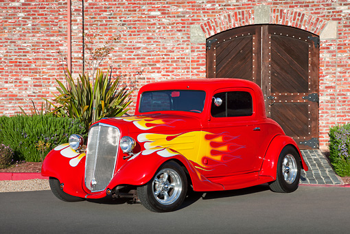 AUT 26 RK3238 01 © Kimball Stock 1934 Chevrolet 3-Window Coupe Red With Flames 3/4 Front View On Pavement By Brick Building