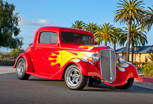 AUT 26 RK3241 01 © Kimball Stock 1934 Chevrolet 3-Window Coupe Red With Flames 3/4 Front View On Pavement By Palm Trees