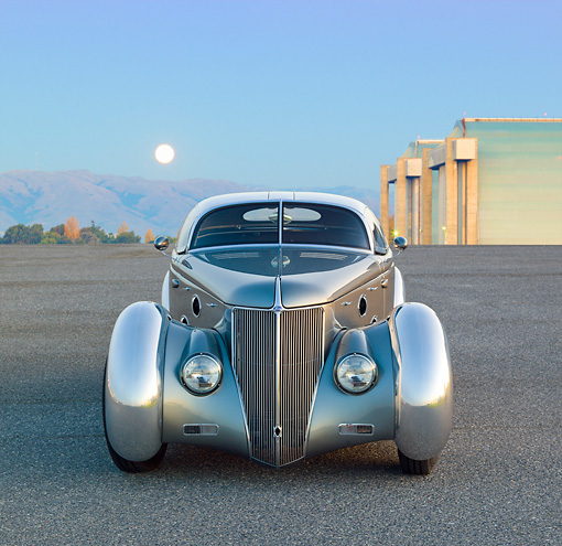 AUT 26 RK3296 01 © Kimball Stock 1936 Ford AeroSport Silver Front View On Pavement By Hangars At Dusk