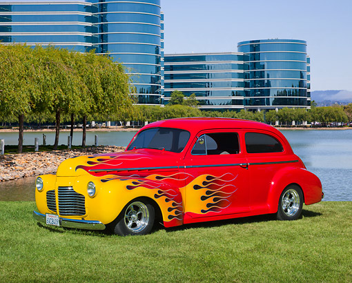 AUT 26 RK3333 01 © Kimball Stock 1941 Chevrolet 2-Door Sedan Red With Flames 3/4 Front View On Grass By Lagoon And Glass Buildings