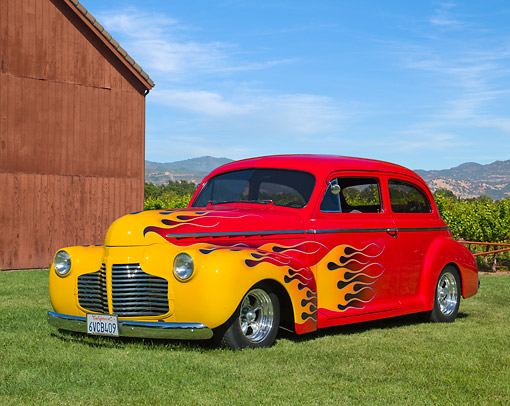 AUT 26 RK3335 01 © Kimball Stock 1941 Chevrolet 2-Door Sedan Red With Flames 3/4 Front View On Grass By Shed And Vineyard