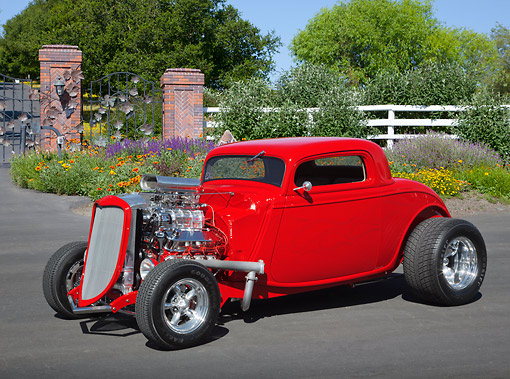 AUT 26 RK3353 01 © Kimball Stock 1934 Ford Coupe Hot Rod Red With Flames 3/4 Front View On Pavement By Flowers And Fence