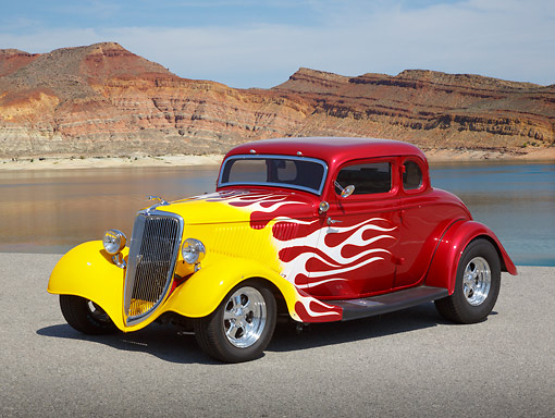 AUT 26 RK3364 01 © Kimball Stock 1934 Ford 5 Window Coupe Red With Flames 3/4 Front View On Pavement By Lake In Desert