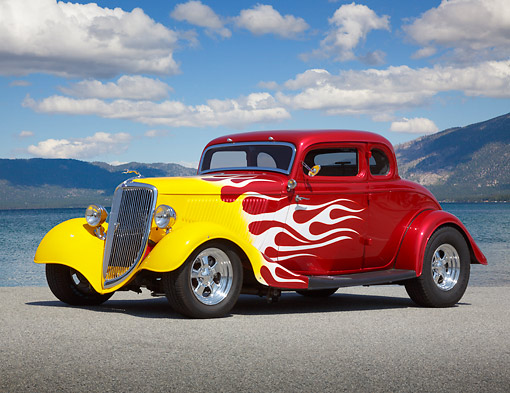 AUT 26 RK3365 01 © Kimball Stock 1934 Ford 5 Window Coupe Red With Flames 3/4 Side View On Pavement By Lake