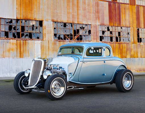 AUT 26 RK3369 01 © Kimball Stock 1934 Ford 5-Window Coupe Blue 3/4 Front View On Pavement By Old Factory Building