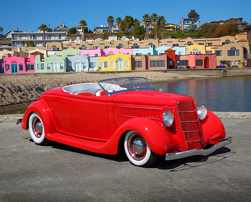 AUT 26 RK3388 01 © Kimball Stock 1935 Ford Roadster Red 3/4 Front View On Pavement By Coloful Houses