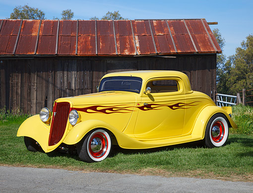 AUT 26 RK3390 01 © Kimball Stock 1938 Chevrolet Yellow With Red Flames 3/4 Front View On Grass By Wooden Shed