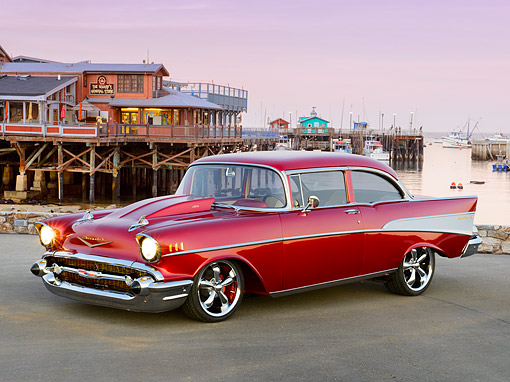 AUT 26 RK3407 01 © Kimball Stock 1957 Chevrolet Bel Air Maroon Candy 3/4 Front View On Pavement By Harbor At Dusk