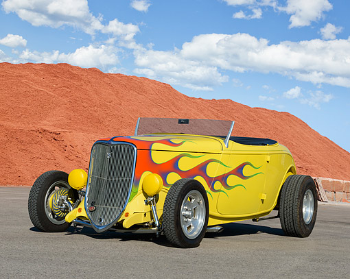 AUT 26 RK3413 01 © Kimball Stock 1933 Ford Roadster Yellow With Flames 3/4 Front View On Pavement By Red Dirt