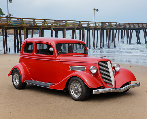 AUT 26 RK3418 01 © Kimball Stock 1933 Ford Vicky Hot Rod Red 3/4 Front View On Sand By Pier