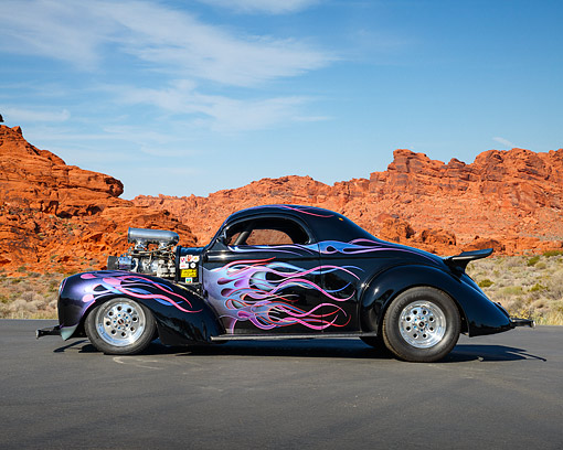 AUT 26 RK3437 01 © Kimball Stock 1947 Willy's Coupe Black With Purple, Pink And Blue Flames Profile View On Pavement By Red Rock
