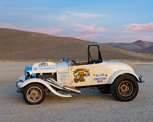 AUT 26 RK3443 01 © Kimball Stock 1929 Ford Model A Roadster Drag Car White Profile View On Pavement By Hills At Dusk