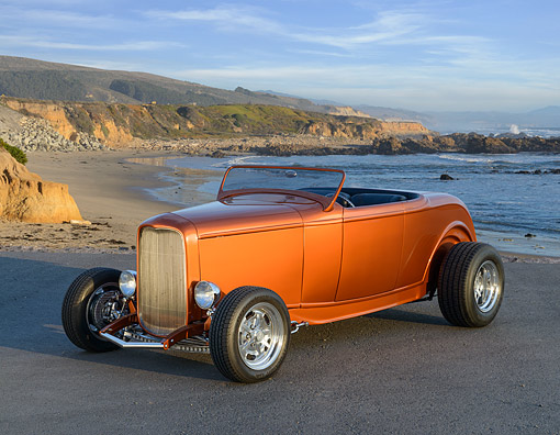 AUT 26 RK3458 01 © Kimball Stock 1932 Ford Roadster Sunburst Orange 3/4 Front View On Pavement By Beach