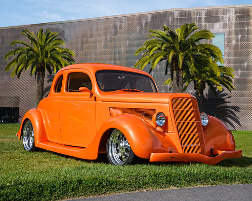 AUT 26 RK3497 01 © Kimball Stock 1935 Ford 5-Window Coupe Tangerine 3/4 Front View On Grass By Building
