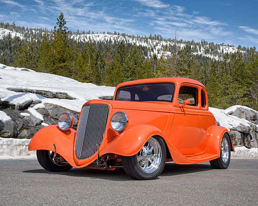 AUT 26 RK3505 01 © Kimball Stock 1934 Ford 5 Window Coupe Hot Rod Orange 3/4 Front View On Road By Snowy Mountain