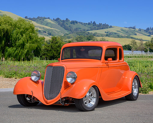AUT 26 RK3506 01 © Kimball Stock 1934 Ford 5 Window Coupe Hot Rod Orange 3/4 Front View On Road Grass And Hills