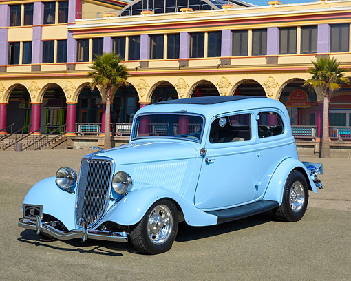 AUT 26 RK3523 01 © Kimball Stock 1934 Ford Victoria Hot Rod Light Blue 3/4 Front View On Beach By Building And Palm Trees