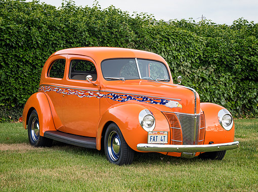 AUT 26 RK3556 01 © Kimball Stock 1940 Ford Hot Rod Orange With Patriotic Flame Graphics 3/4 Front View On Grass By Bushes