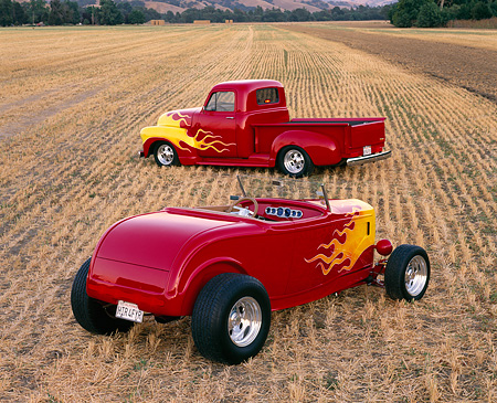AUT 26 RK0046 03 © Kimball Stock 1932 Ford Roadster & 1952 Chevrolet Pickup Red Yellow Flames 3/4 Rear View In Farm Field