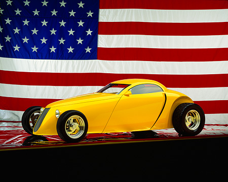 AUT 26 RK0059 02 © Kimball Stock Aluma Coupe Yellow 3/4 Side View American Flag Background