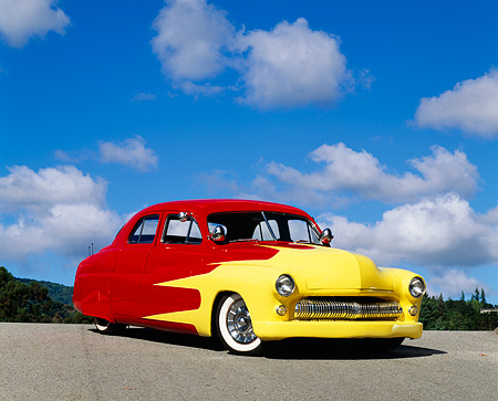 AUT 26 RK0071 02 © Kimball Stock 1950 Mercury Custom Red And Yellow Low 3/4 Front View On Pavement Hill Cloudy Blue Sky