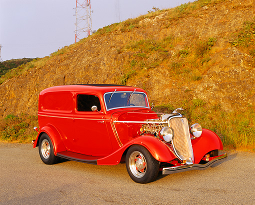 AUT 26 RK0179 03 © Kimball Stock 1933 Ford Delivery Sedan Red 3/4 Front View On Pavement By Dry Grass Hill