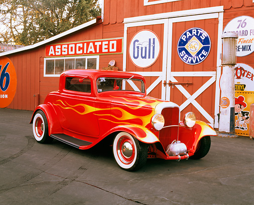 AUT 26 RK0192 01 © Kimball Stock 1932 Ford 3-Window Coupe Red With Flames 3/4 Front View On Pavement By Barn