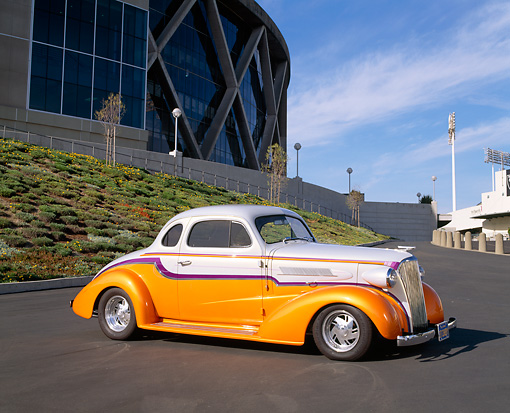 AUT 26 RK0202 05 © Kimball Stock 1937 Chevrolet Master Coupe Orange And White 3/4 Front View On Pavement By Stadium