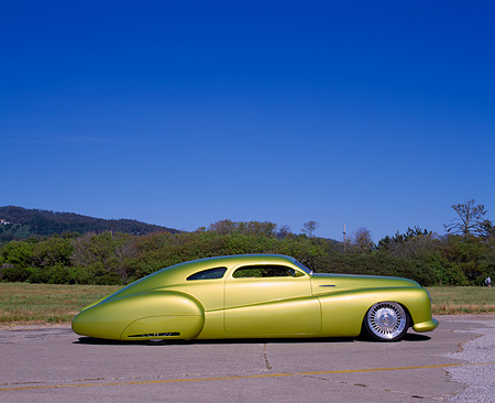 AUT 26 RK0233 01 © Kimball Stock 1948 Buick Roadmaster Custom Green Profile On Pavement By Grass Bushes Blue Sky