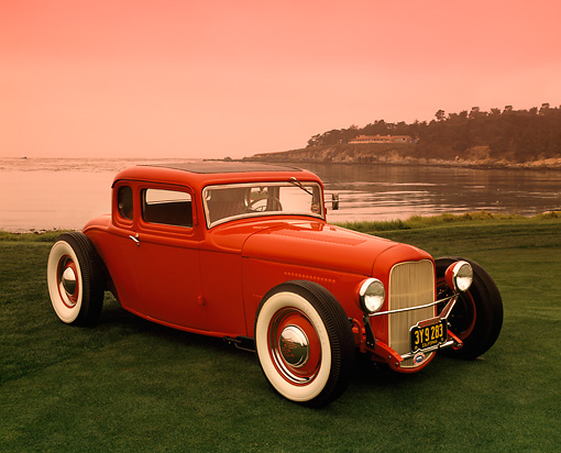 AUT 26 RK0253 03 © Kimball Stock 1932 Ford Coupe Red 3/4 Side View On Grass By Water Red Sky