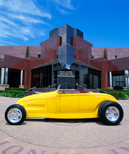 AUT 26 RK0259 01 © Kimball Stock 1929 Ford Highboy Yellow Low Profile On Pavement By Museum Blue Sky