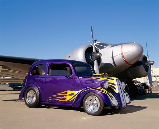 AUT 26 RK0270 03 © Kimball Stock 1951 Ford Anglia Purple With Flames 3/4 Front View On Pavement By Military Airplane Blue Sky