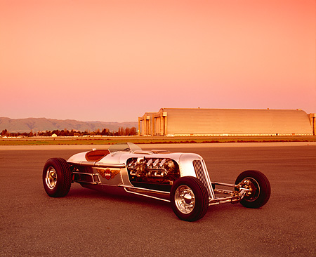 AUT 26 RK0286 02 © Kimball Stock Blastolene Special Concept Race Car 3/4 Front View On Pavement Airplane Hanger Background Filtered