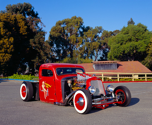 AUT 26 RK0365 01 © Kimball Stock 1937 Chevy Rat Rod Red 3/4 Front View On Pavement By Trees