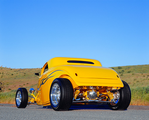 AUT 26 RK0378 02 © Kimball Stock 2004 Speed Star Coupe Yellow Blue Flames 3/4 Rear View On Pavement By Grass Hill