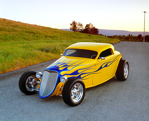 AUT 26 RK0381 01 © Kimball Stock 2004 Speed Star Coupe Yellow Blue Flames 3/4 Front View On Pavement By Grass Hill Filtered