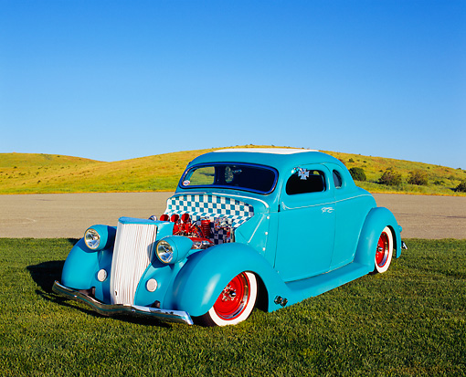 AUT 26 RK0389 05 © Kimball Stock 1936 Ford Custom Coupe Light Blue 3/4 Front View On Grass Blue Sky