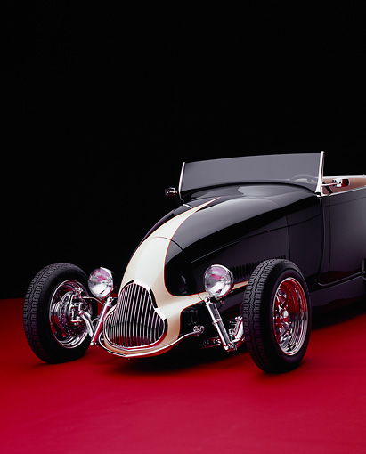AUT 26 RK0539 09 © Kimball Stock 1929 Ford Track Nose Roadster Black And Cream Front 3/4 View On Red Floor Studio