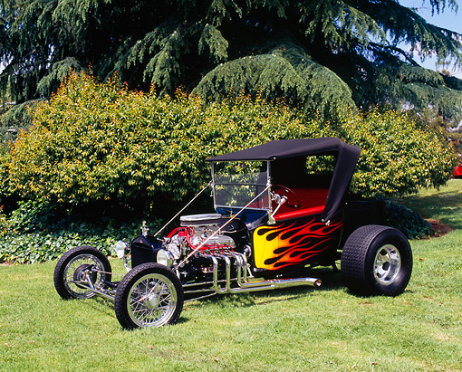 AUT 26 RK0558 03 © Kimball Stock 1923 Ford Roadster Pickup Truck Hot Rod Black With Flames 3/4 Front View On Grass By Shrubs Trees