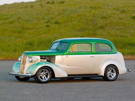 AUT 26 RK0668 01 © Kimball Stock 1937 Chevrolet Sedan Green And White 3/4 Side View On Pavement By Grass Hill