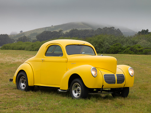 AUT 26 RK1154 01 © Kimball Stock 1940 Willys 440 Coupe Yellow 3/4 Front View On Grass