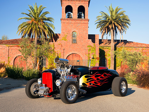 AUT 26 RK1199 01 © Kimball Stock 1929 Ford Roadster Hot Rod Black With Flames Front 3/4 View On Pavement By Building Palm Trees